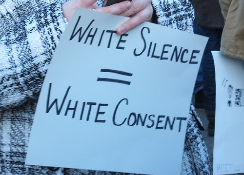 A caucasian protester presumably at a #BlackLivesMatter protest holds a sign stating that White Silence = White Consent.